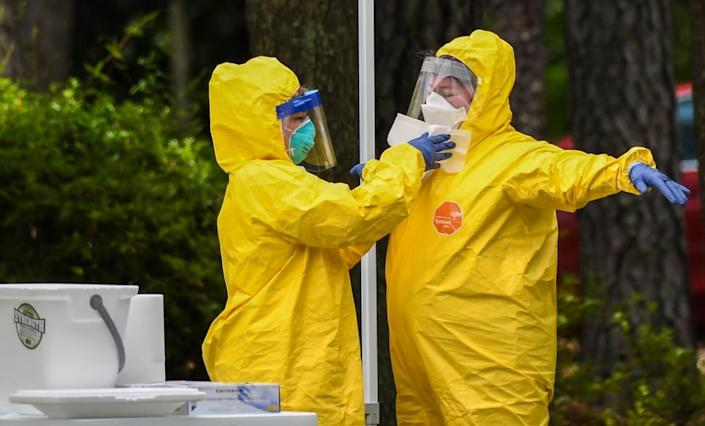 A worker uses disinfectant wipes to clean the personal protective equipment of a worker who just administered a nose swab at the free COVID-19 test site on Thursday, May 28, 2020 at the Elijah Washington Medical Center in Sheldon.