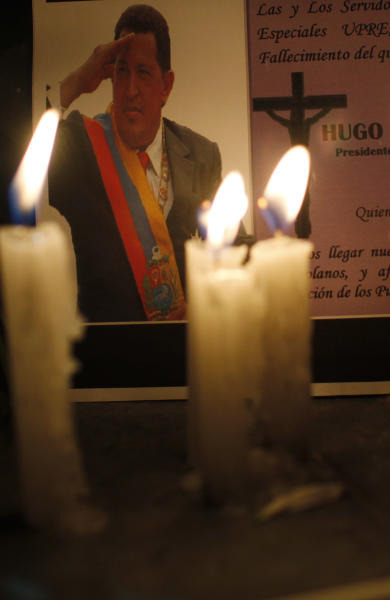 FILE - In this March 5, 2013 file photo, candles, placed by mourner demonstrators, burn in front of an image of Venezuela's President Hugo Chavez outside the Venezuela's embassy in La Paz, Bolivia. For his loyal followers, Chavez was already a living legend on par with independence era hero Simon Bolivar even before his March 5 death from cancer. In a mere three weeks, however, Chavez has ascended to divine status, at least according to political rhetoric, as the government and his die-hard loyalists build a religious mythology around him ahead of April 14 elections scheduled to pick a new leader. (AP Photo/Juan Karita, File)