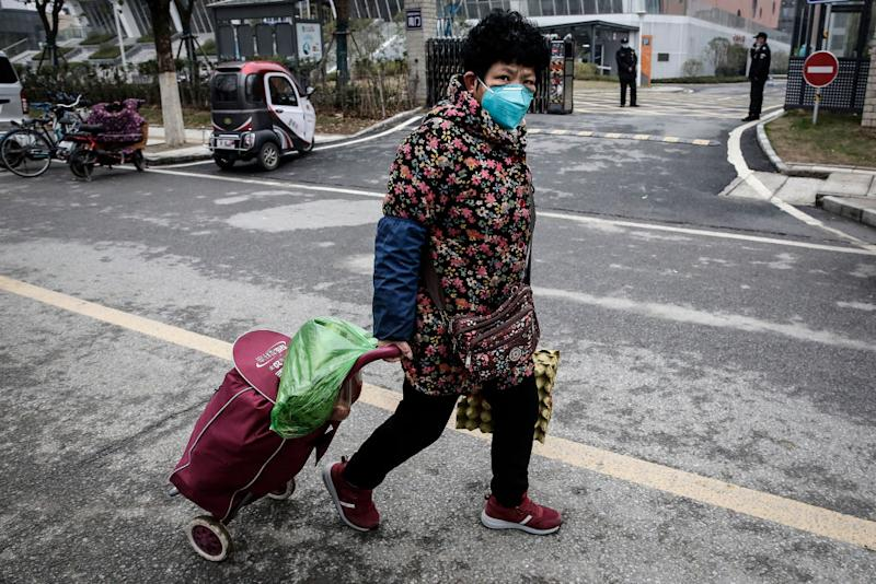 Pictured is an elderly woman with a trolley and a mask on a Wuhan street.