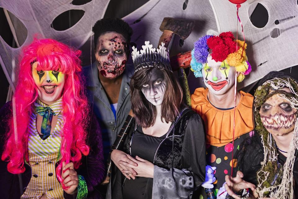 A group of young adults dressed in scary halloween costumes, zombies, demons, ghouls and a clown. They are working in a haunted house, ready to scare any trespassers.