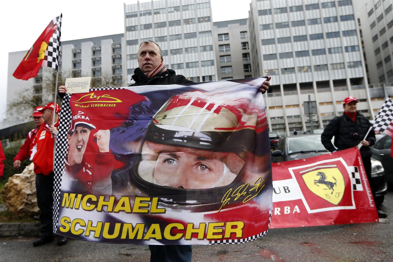Philippe, a fan from Lyon, waves a flag as he attends a silent 45th birthday tribute to seven-times former Formula One world champion Michael Schumacher with Ferrari fans in front of the CHU hospital emergency unit in Grenoble, French Alps, where Michael Schumacher is hospitalized January 3, 2014. His agent said on Wednesday that Michael Schumacher was in a stable condition and it was too early to talk about his further prospects. No further update was given on Thursday, the day before his 45th birthday. Schumacher is battling for his life after slamming his head against a rock while skiing off-piste in the French resort of Meribel on Sunday. REUTERS/Charles Platiau (FRANCE - Tags: SPORT MOTORSPORT HEALTH)