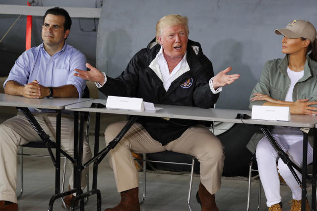 Trump sits between Puerto Rico Governor Ricardo Rossello and first lady Melania Trump as he receives a briefing on hurricane damage in Carolina, Puerto Rico, on Oct. 3. (Photo: Jonathan Ernst/Reuters)