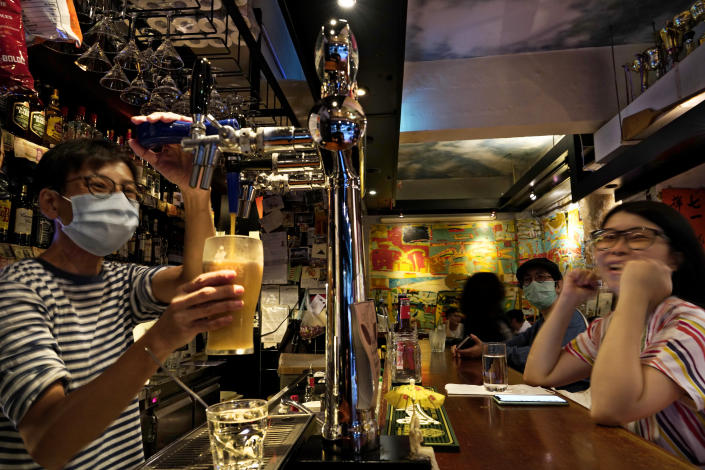 In this Oct. 7, 2020 photo, an employee serves a beer to a customer at Club 71 in Hong Kong. The bar known as a gathering place for pro-democracy activists and intellectuals is closing. For years, the storied bar has served as a watering hole for the city's pro-democracy activists and intellectuals, who could freely engage in discussions over a round of beer or two. (AP Photo/Vincent Yu)
