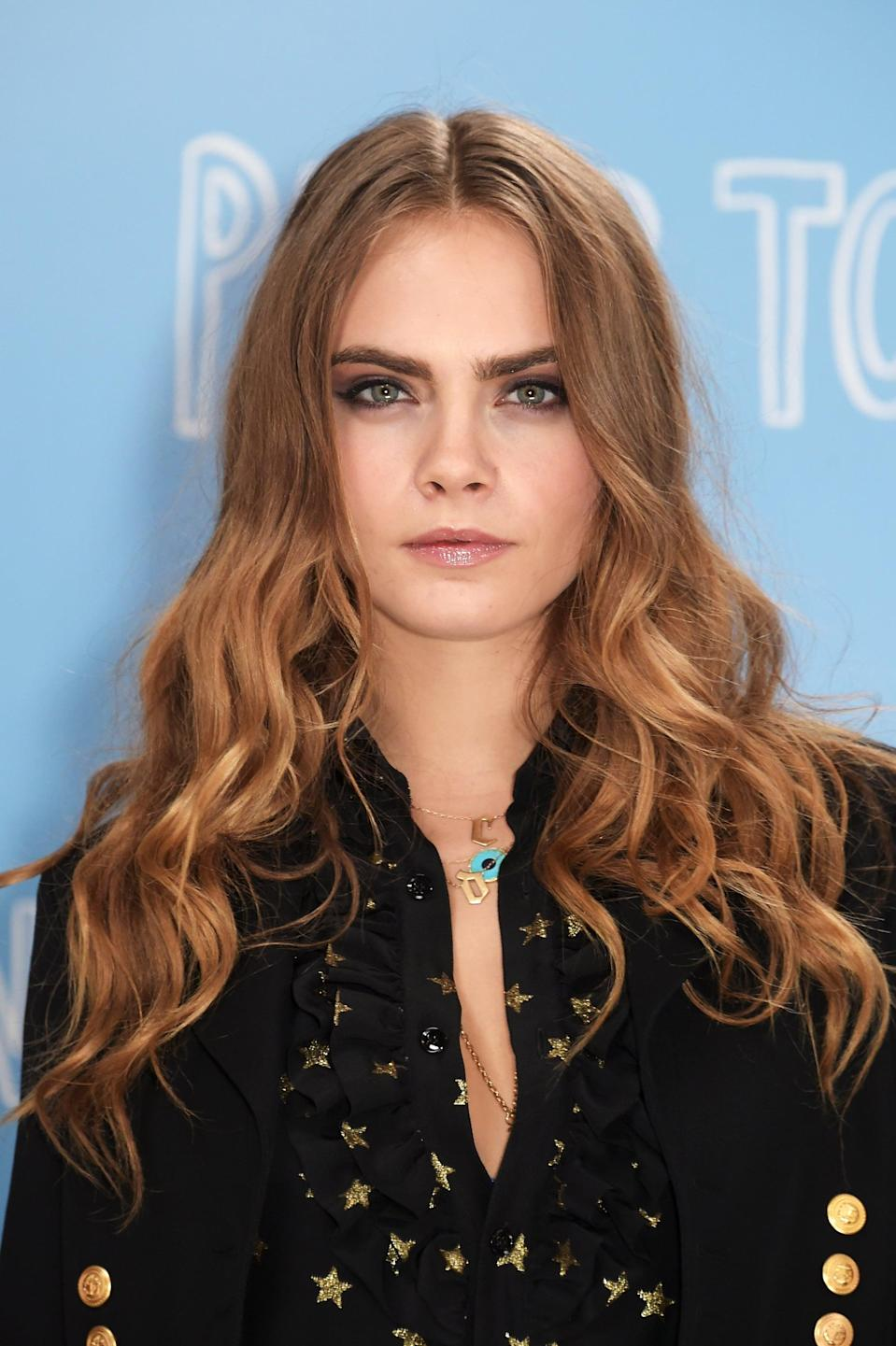 <p>Her hair dyed a warm shade of honey blond, Delevingne's curls took a tighter turn at a <strong>Paper Towns</strong> photocall. </p>