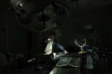 A nurse uses light from a phone while he looks for material in an out-of-use operating room of the Padre Justo hospital, during a blackout in Rubio, Venezuela March 14, 2018. Picture taken March 14, 2018. REUTERS/Carlos Eduardo Ramirez