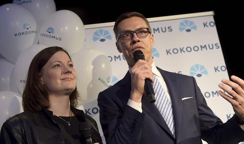 Alexander Stubb (R) and party secretary Minna Arve speak on stage after the announcing of the pre-elections votes at the party's parliamentary elections reception in Helsinki on April 19, 2015 (AFP Photo/Vesa Moilanen)