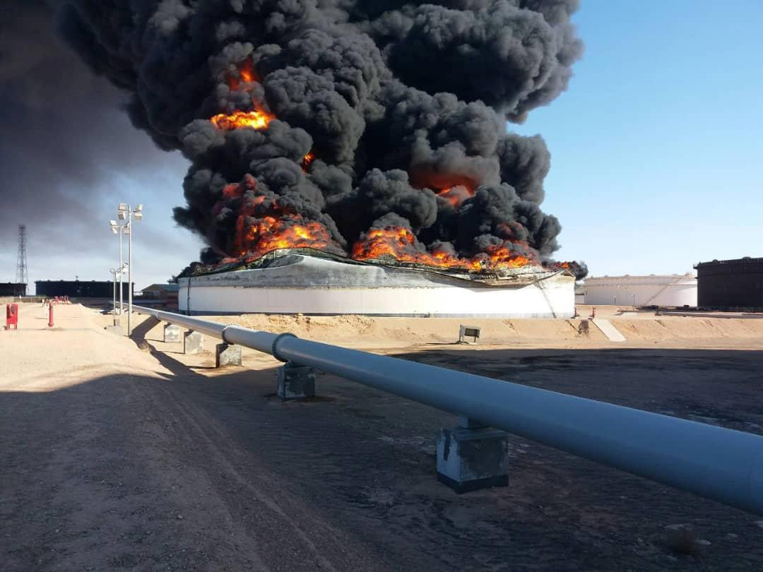 Smoke and flame rise from an oil storage tank that was set on fire amid fighting between rival factions at Ras Lanuf terminal, Libya in this handout picture released on June 18, 2018. The National Oil Corporation/ Handout via Reuters ATTENTION EDITORS - THIS PICTURE WAS PROVIDED BY A THIRD PARTY. REUTERS IS UNABLE TO INDEPENDENTLY VERIFY THIS IMAGE.
