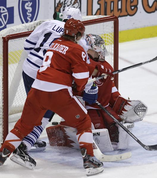 Toronto Maple Leafs right wing Joffrey Lupul (19), defended by Detroit Red Wings left wing Justin Abdelkader (8) gets the puck past goalie Jimmy Howard for a goal during the second period of an NHL hockey game in Detroit, Friday, Sept. 27, 2013. (AP Photo/Carlos Osorio)