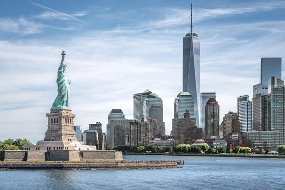 The New York City landscape, with the Statue of Liberty and World Trade Center visible.