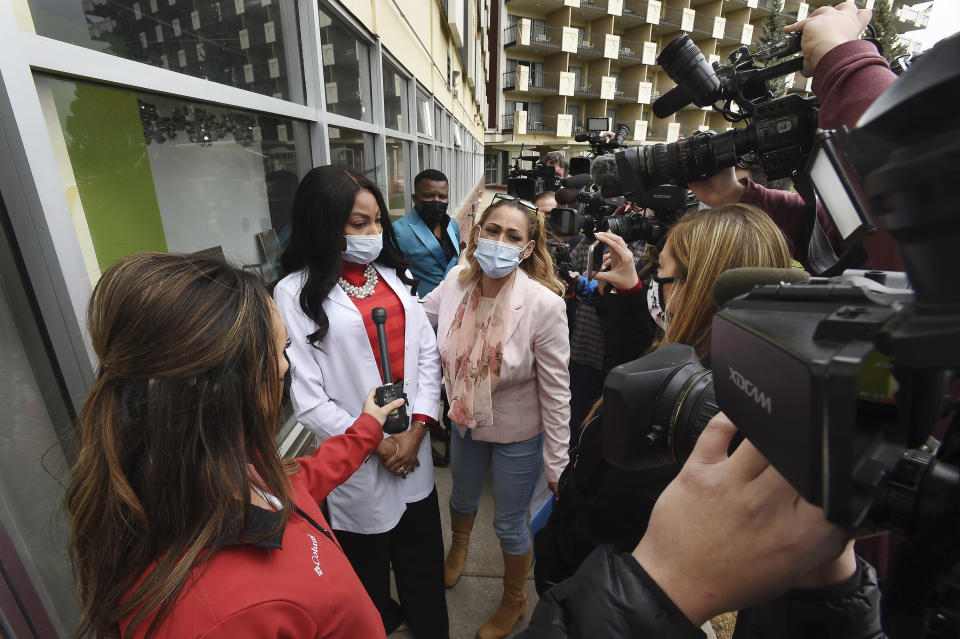FILE - In this April 19, 2021, file photo Dr. Sylvienash Moma, second left, with hands clasped, declines to speak with the media, outside the Dr. Moma Health & Wellness Clinic at the Satellite Hotel in Colorado Springs, Colo., to address questions that the clinic allegedly improperly stored vaccines, prompting a state investigation. Colorado's health department is recommending that people who received their COVID-19 vaccines at the clinic get revaccinated after a state investigation found the facility improperly stored and handled vaccine doses. The department said Friday, Oct. 8, 2021, it also is permanently banning the clinic from any participation in the federal government's vaccination campaign. (Jerilee Bennett/The Gazette via AP, File)