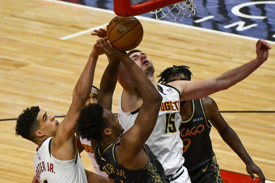 Chicago Bulls center Wendell Carter Jr., center, fights for the ball with Denver Nuggets forward Michael Porter Jr., left, forward Will Barton, back, and center Nikola Jokic, (15), during the first half of an NBA basketball game Monday, March 1, 2021, in Chicago. (AP Photo/Matt Marton)