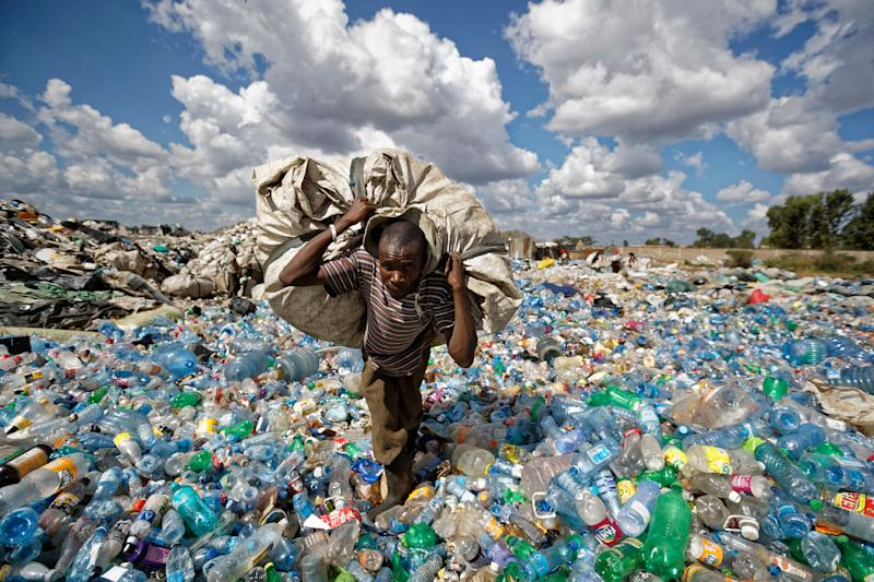 A man walks on a mountain of plastic bottles as he carries a sack of them to be sold for recycling after weighing them at the dump in the Dandora slum of Nairobi, Kenya. (Photo: AP Photo/Ben Curtis)