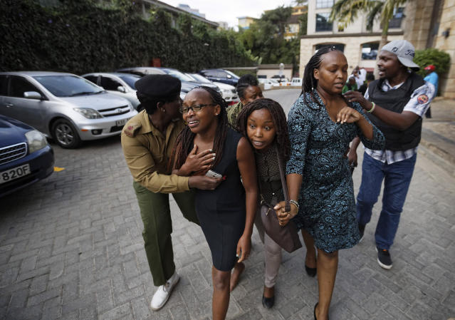 Civilians flee the scene at a hotel complex in Nairobi, Kenya Tuesday, Jan. 15, 2019. An upscale hotel complex in Kenya's capital came under attack on Tuesday, with a blast and heavy gunfire. The al-Shabab extremist group based in neighboring Somalia claimed responsibility and said its members were still fighting inside. (AP Photo/Ben Curtis)
