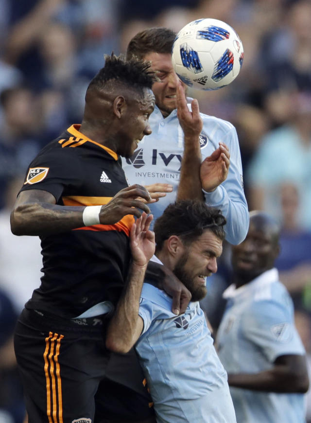 Houston Dynamo forward Romell Quioto, left, heads the ball against Sporting Kansas City midfielders Graham Zusi, lower right, and Ilie Sanchez, upper right, during the first half of an MLS soccer match in Kansas City, Kan., Saturday, June 23, 2018. (AP Photo/Orlin Wagner)