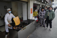 Residents wearing masks to help curb the spread of the coronavirus queue up at a popular food stall in Wuhan, China, Tuesday, Jan. 26, 2021. The central Chinese city of Wuhan, where the coronavirus was first detected, has largely returned to normal but is on heightened alert against a resurgence as China battles outbreaks elsewhere in the country. (AP Photo/Ng Han Guan)