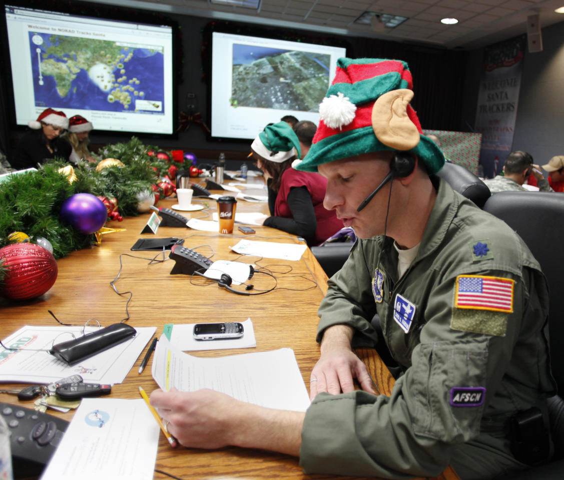 FILE - In this Dec. 24, 2010 file photo, Air Force Lt. Col. David Hanson, of Chicago, takes a phone call from a child in Florida at the Santa Tracking Operations Center at Peterson Air Force Base near Colorado Springs, Colo. Santa is already piling up monster numbers on social networking sites this season, so the volunteer Santa-trackers at NORAD are bracing for tens of thousands of calls and emails when their operations center goes live on Christmas Eve. (AP Photo/Ed Andrieski)