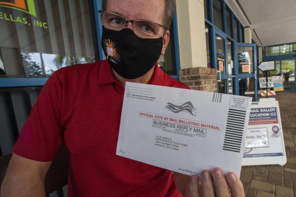 Charles Oppermann holds his vote by mail ballot for Joe Biden outside the drop-off location at the Dunedin Public Library Thursday, Oct. 29, 2020, in Dunedin, Fla. Oppermann, 55, is most anxious that the results of the election will turn into a prolonged fight. As Election Day closes in, Americans are exhausted from constant crises, on edge because of volatile political divisions and anxious about what will happen next.(AP Photo/Steve Nesius)