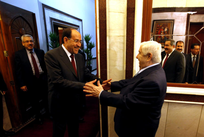 Syrian Foreign Minister Walid al-Moallem, right, shakes hands with the Iraqi Prime Minister Nouri al-Maliki prior to a meeting in Baghdad, Iraq, Sunday, May. 26, 2013. (AP Photo/Hadi Mizban, Pool)