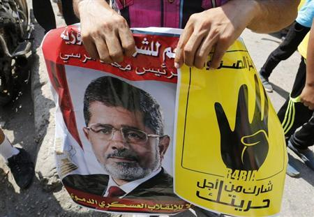 Supporters of Mursi hold his picture and a poster during a protest against the military and the interior ministry in Cairo