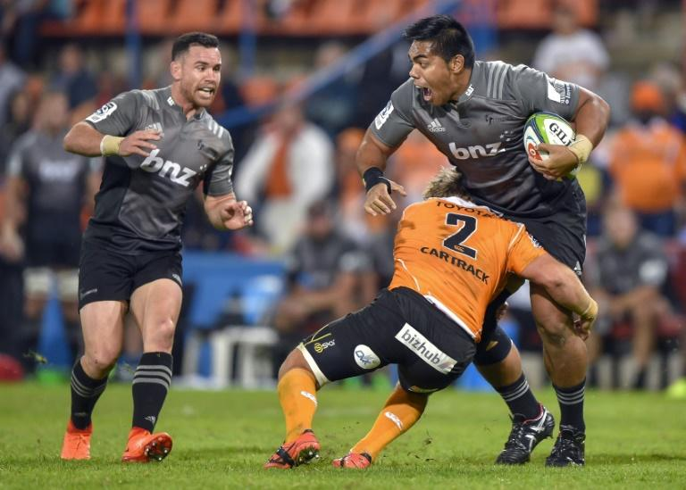 The Central Cheetahs' Torsten van Jaarsveld (C) tackles the Canterbury Crusaders' Seta Tamanivalu during their Super Rugby match, at the Bloemfontein stadium in South Africa, on April 29, 2017