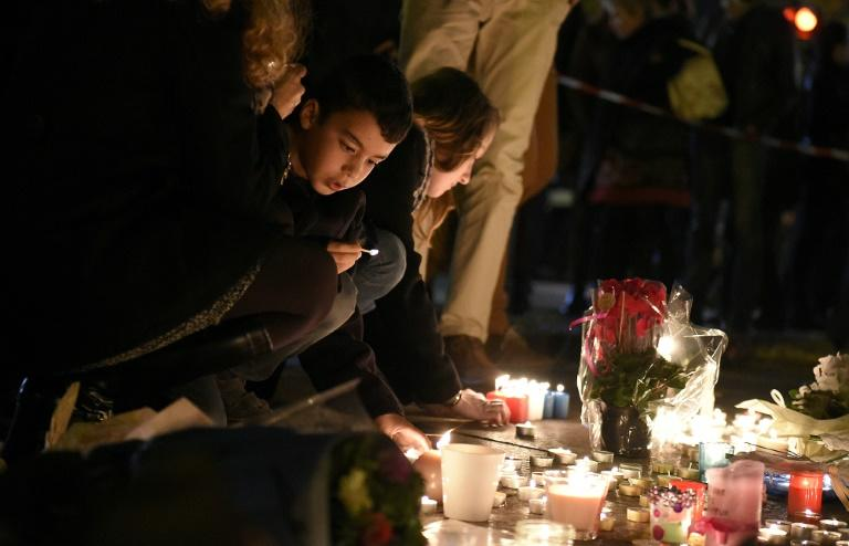 A child leaves flowers at a makeshift memorial as people pay homage to attack victims near Bataclan concert hall on November 14, 2015 in Paris, a day after a series of coordinated attacks left at least 129 people dead