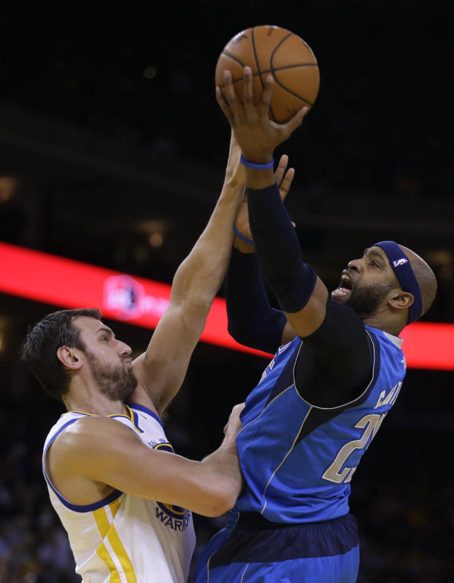 Dallas Mavericks' Vince Carter, right, shoots over Golden State Warriors' Andrew Bogut during the first half of an NBA basketball game Tuesday, March 11, 2014, in Oakland, Calif. (AP Photo/Ben Margot)