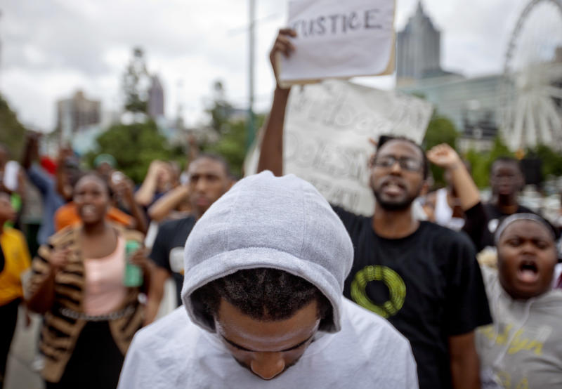 A demonstrator wears a hoodie during a protest the day after George Zimmerman was found not guilty in the 2012 shooting death of teenager Trayvon Martin, Sunday, July 14, 2013, in Atlanta. (AP Photo/David Goldman)