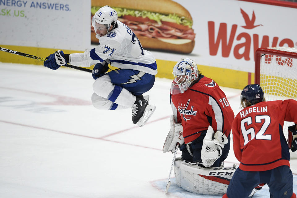 Tampa Bay Lightning center Anthony Cirelli (71) leaps in front of Washington Capitals goaltender Braden Holtby (70) during the third period of an NHL hockey game, Saturday, Dec. 21, 2019, in Washington. Capitals left wing Carl Hagelin (62) looks on. (AP Photo/Nick Wass)