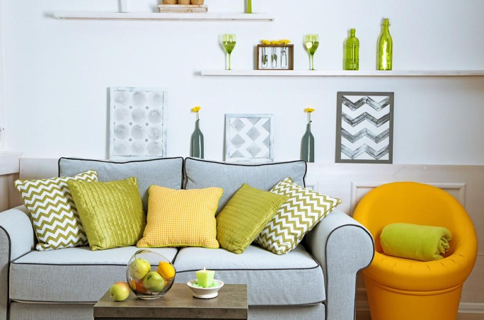 modern living room with gray couch, yellow chair, crowded walls with open shelving, and cluttered table