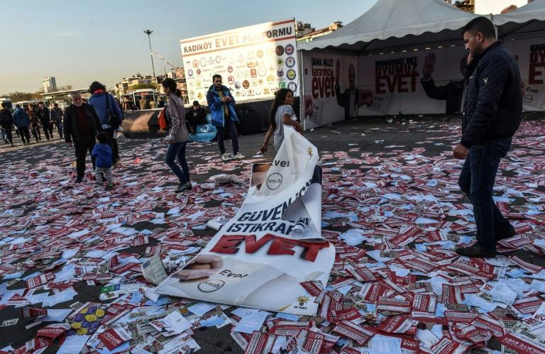 "A girl drags a banner reading ""yes"" across piles of ""yes"" leaflets in the Kadikoy district of Istanbul"
