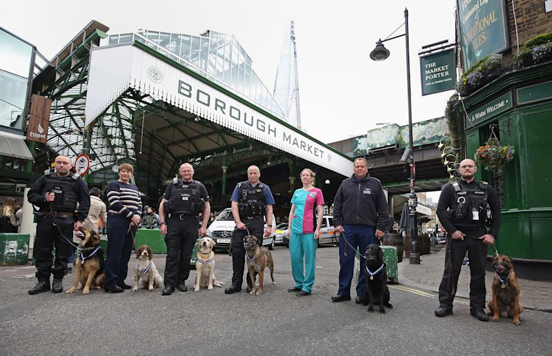 (Left to right) PD Marci with handler PC Neil Billany, PD Kai with handler PC Jean Pearce, PD Bruno with handler Rob Smith, PD Delta with handler PC Mark Snoxhall, PDSA vet Rosamund Ford, PD Dave with handler PC Andy Salter and PD Jax with handler PC Craig Howarth at Borough market in London where the dogs were honoured with the PDSA Order of Merit for helping emergency services during the 2017 London terror attacks at Westminster Bridge, London Bridge and Borough Market.