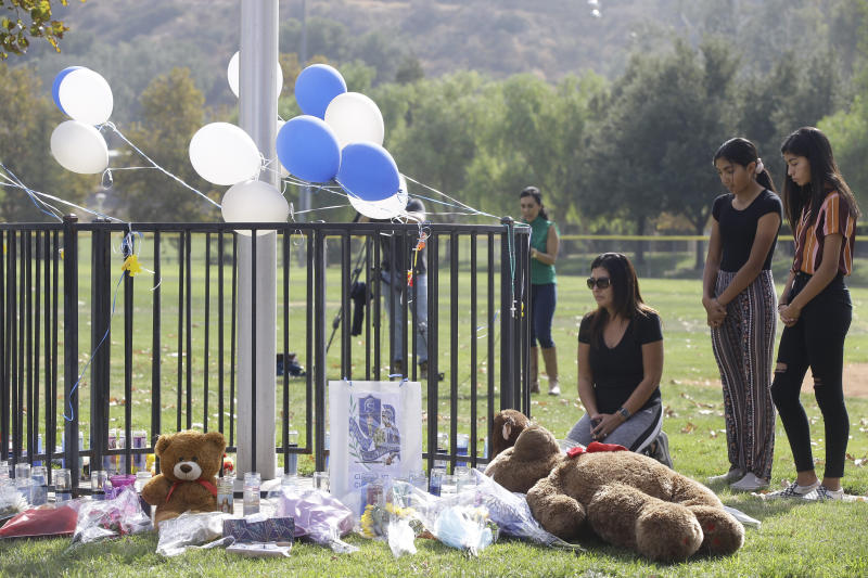 Parent Mirna Herrera kneels with her daughters Liliana, 15, and Alexandra, 16 at the Central Park memorial for the Saugus High School victims in Santa Clarita, Calif., Friday, Nov. 15, 2019. Investigators said Friday they have yet to find a diary, manifesto or note that would explain why a boy killed two students outside his Southern California high school on his 16th birthday. (AP Photo/Damian Dovarganes)