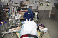 Medical staff start the preparations for the surgery of Caroline Erganian at Bichat Hospital, AP-HP, in Paris, Wednesday, Dec. 2, 2020. Erganian, 58, hopes to shed more than a third of her weight as a result of having a large part of her stomach cut out and be free of knee and back pain — and of her cane. She prayed in the final weeks that her phone wouldn't ring with news of another delay. (AP Photo/Francois Mori)