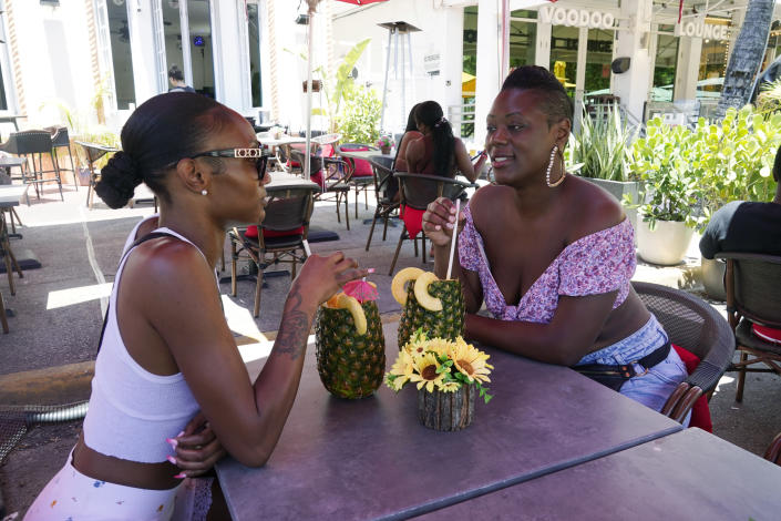 Ar'Tell Young, left, and Marlena Lee, enjoy a tropical drink Wednesday, May 26, 2021, in Miami Beach, Fla. America's tourist destinations are facing a severe worker shortage just as they try to rebound from a devastating year lost to the pandemic. (AP Photo/Marta Lavandier)