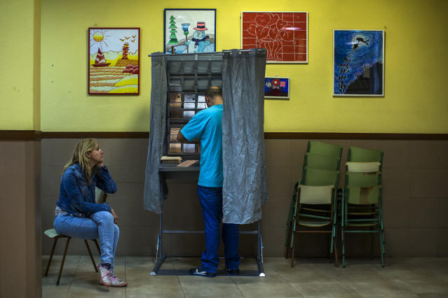 <p>A man prepares to vote as his partner and two children wait at a polling station in Madrid, May 24, 2015. (AP Photo/Andres Kudacki) </p>