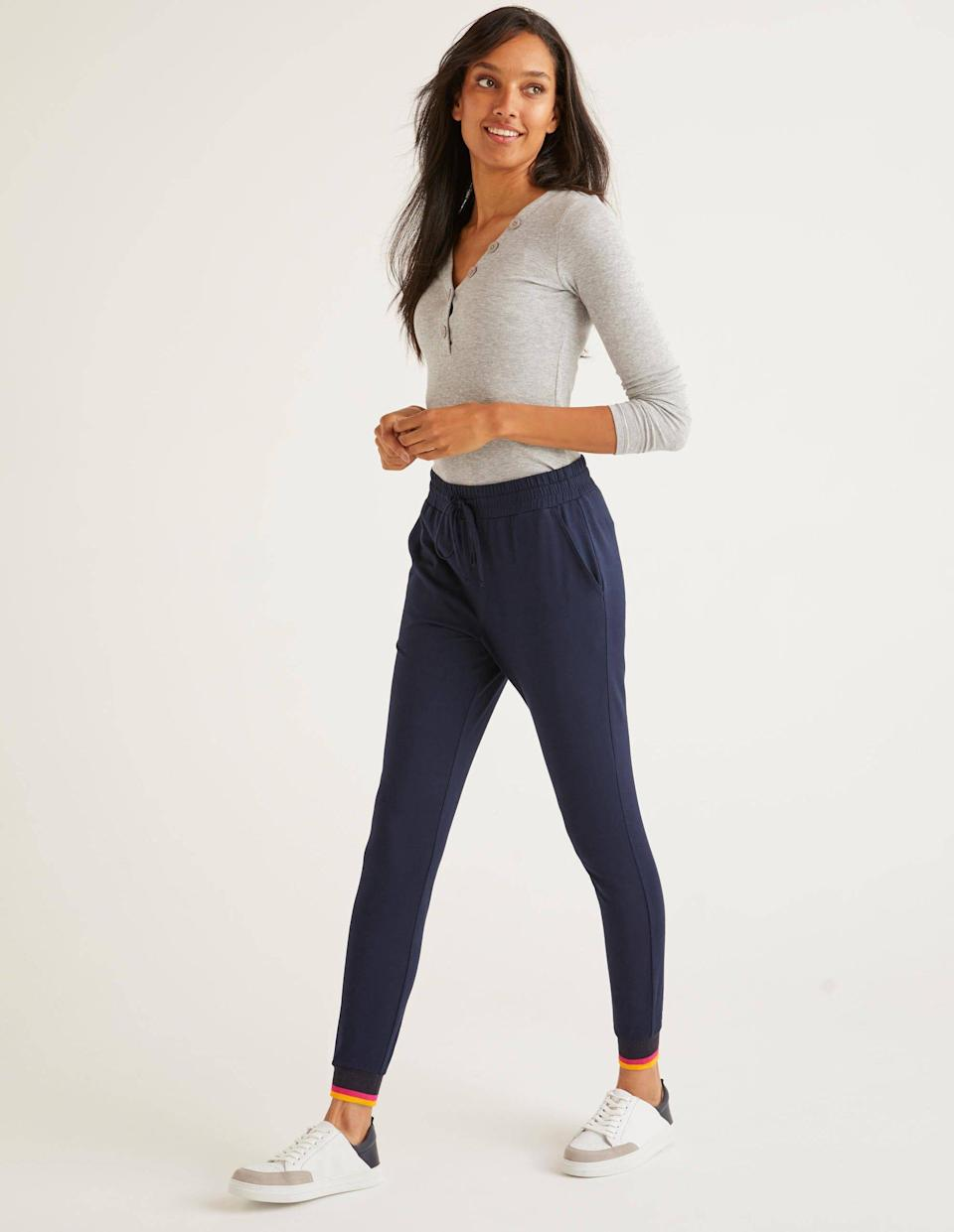 """<p>The fit of these Boden Cuffed Jersey Joggers is a hybrid between a sweatpant and a legging, with a drawstring waist that will come in handy right after that snack break. The orange and yellow stripes at the ankles are a nice touch of color against the classic navy. This style comes in six colors, which makes it even more perfect for stockpiling as your new go-to bottom. </p> <p><strong>Sizes available:</strong> XS to XL</p> <p><strong>$44</strong> (<a href=""""https://www.bodenusa.com/en-us/cuffed-jersey-joggers-navy/sty-j0612-nav?cat=C1_S2_G114"""" rel=""""nofollow noopener"""" target=""""_blank"""" data-ylk=""""slk:Shop Now"""" class=""""link rapid-noclick-resp"""">Shop Now</a>) </p>"""