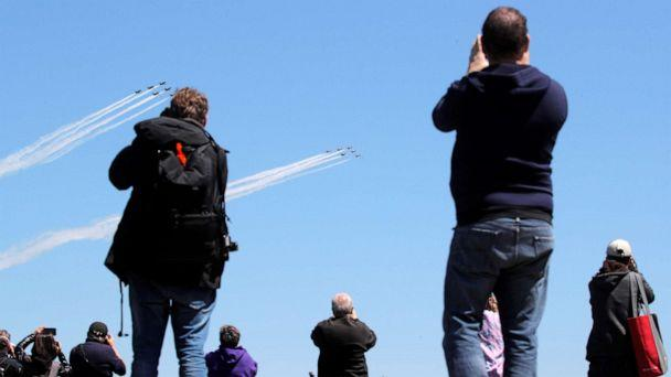 PHOTO: People watch as U.S. Navy Blue Angels and U.S. Air Force Thunderbirds demonstration teams participate in a midday flyover of New York City region to honor first responders and essential workers during the coronavirus pandemic, April 28, 2020. (Brendan McDermid/Reuters)