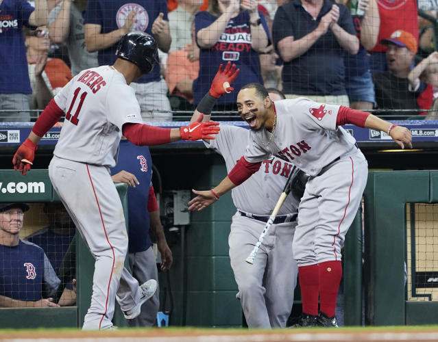 Boston Red Sox's Rafael Devers (11) celebrates with Mookie Betts, right, after hitting a home run against the Houston Astros during the fourth inning of a baseball game Sunday, May 26, 2019, in Houston. (AP Photo/David J. Phillip)