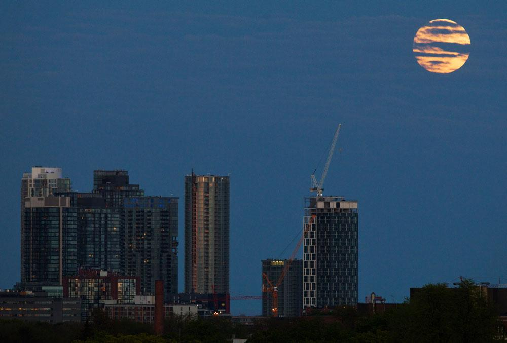 "The ""supermoon"" rises over some apartment buildings in Toronto, May 5, 2012. A ""supermoon"" will light up Saturday's night sky in a once-a-year cosmic show, overshadowing a meteor shower from remnants of Halley's Comet, the U.S. space agency NASA said. The Moon will seem especially big and bright since it will reach its closest spot to Earth at the same time it is in its  full phase, NASA said."