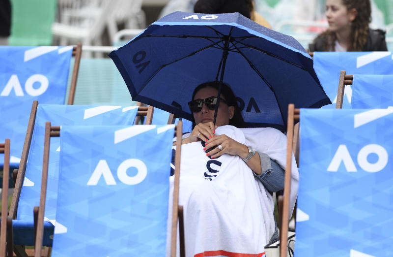 A spectator sits under an umbrella as rain stops play on the outside courts during the first round singles matches at the Australian Open tennis championship in Melbourne, Australia, Monday, Jan. 20, 2020. (AP Photo/Andy Brownbill)