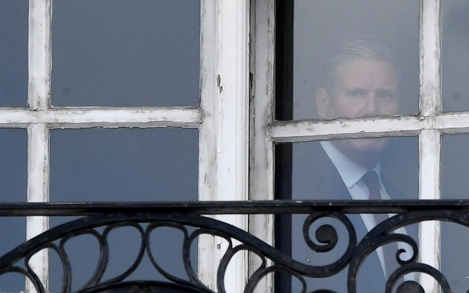 Keir Starmer is seen in the window of his offices in London - TOBY MELVILLE/REUTERS