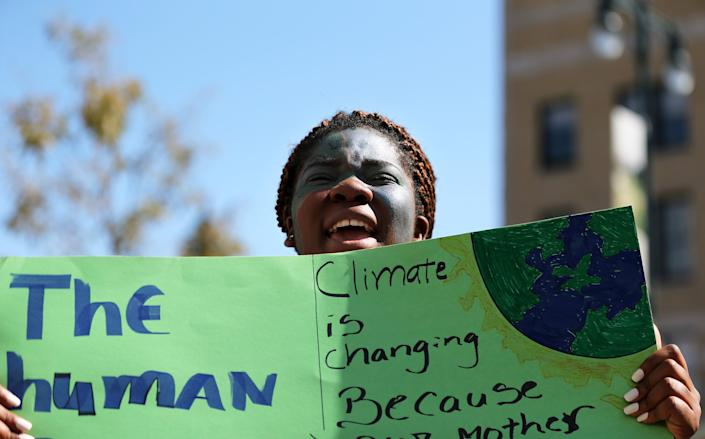 Ruscirene Dinanga, a junior from Portland High School, chants with a crowd of more than 2,000 outside of Portland City Hall on Friday to demand more aggressive action to combat climate change.