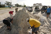 Local residents fill sand bags as they prepare for the expected arrival of Hurricane Ida Saturday, Aug. 28, 2021, in Gulfport, Miss. (AP Photo/Steve Helber)