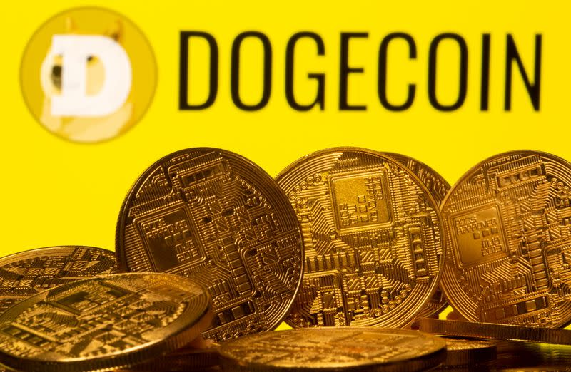 FILE PHOTO: Cryptocurrency representations are seen in front of the Dogecoin logo in this illustration