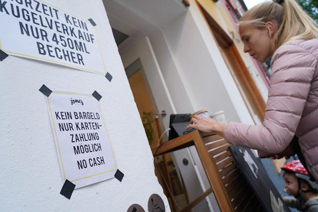 A sign notifies customers of no cash payments as a customer pays with a credit card at a shop in Schoeneberg district, in Berlin, Germany. (Sean Gallup/Getty Images)