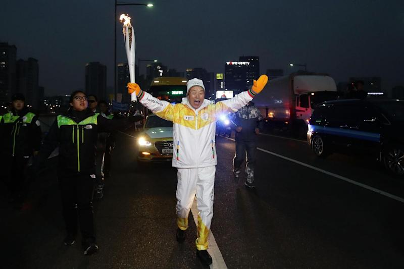 A torchbearer carries the PyeongChang 2018 Winter Olympics torch through Seoul, South Korea (Getty Images)