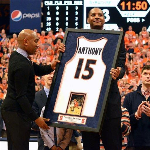 Syracuse athletic director Daryl Gross, left, presents Carmelo Anthony with a jersey during a jersey retirement ceremony at halftime of Syracuse's NCAA college basketball game against Georgetown in Syracuse, N.Y., Saturday, Feb. 23, 2013. (AP Photo/Kevin Rivoli)