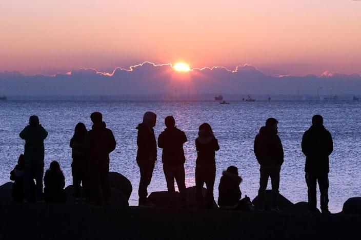 People watch the sun rise on New Year's Day over Tokyo Bay on January 1, 2016 (AFP Photo/Yoshikazu Tsuno)