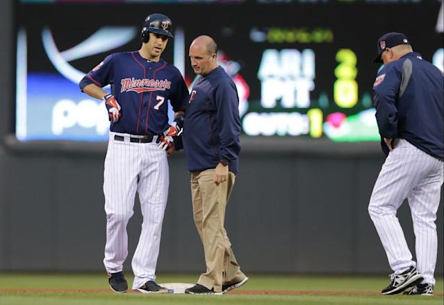 Minnesota Twins' Joe Mauer, left, is checked by a trainer as manager Ron Gardenhire, right, comes out after Mauer's two-run double off Kansas City Royals pitcher James Shields in the fourth inning of a baseball game, Tuesday, July 1, 2014, in Minneapolis. Mauer later left the game. (AP Photo/Jim Mone)