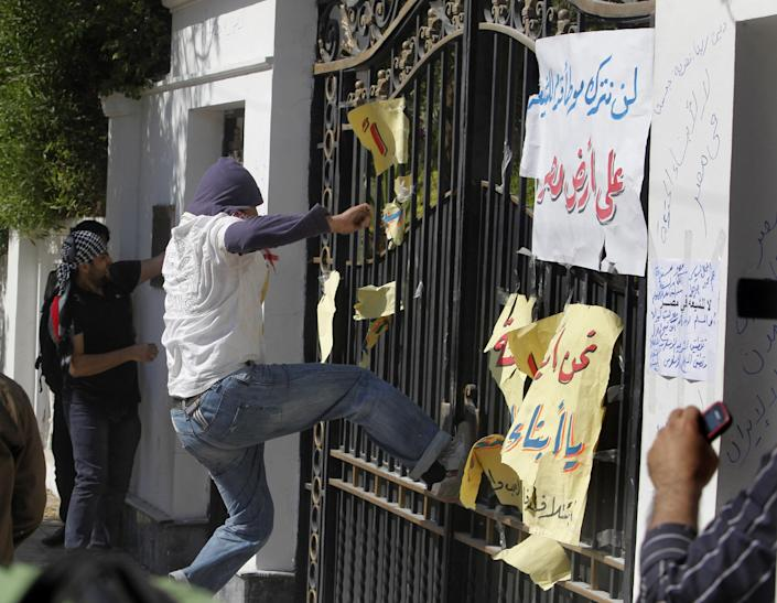 """Egyptian protesters try to destroy the gate at the residence of Iran's top diplomat in Cairo, Egypt, Friday, April 5, 2013. The protest was sparked after Iranian tourists arrived in Egypt this week on the first commercial flights between the two countries in 30 years. Arabic reads,""""we will not let Shiites step in Egypt."""" (AP Photo/Amr Nabil)"""